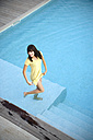 Happy young woman standing in swimming pool - TOYF001066