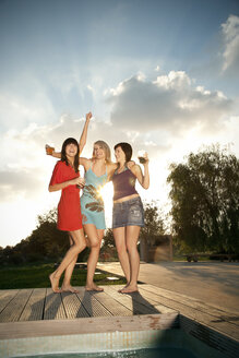 Three happy young women having a party at the poolside - TOYF001076