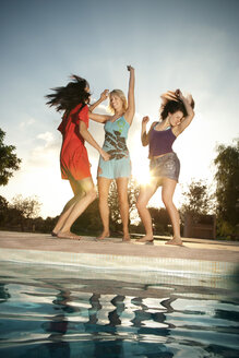 Three exuberant young women having a party at the poolside - TOYF001079