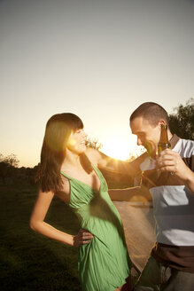 Happy young couple dancing with beer bottle at sunset - TOYF001088