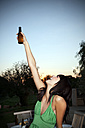 Happy young woman lifting a beer at sunset - TOYF001095