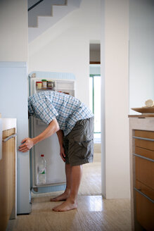 Young man standing in the kitchen searching something in the fridge - TOYF001106