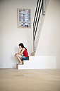 Pensive young woman sitting on steps in a light room - TOYF001109