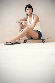 Portrait of young woman sitting on her longboard - TOYF001135