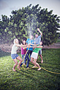 Five friends splashing with water in the garden - TOYF001149