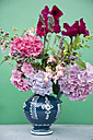 Bunch of flowers in a jar in front of green wall - GISF000135