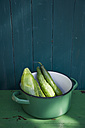 Green enamel cooking pot with cucumbers and courgette in front of wooden wall - GISF000138