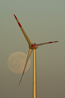 Germany, full moon at evening twilight with wind wheel in the foreground - UMF000787