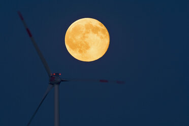 Germany, rise of full moon with wind wheel in the foreground - UMF000792
