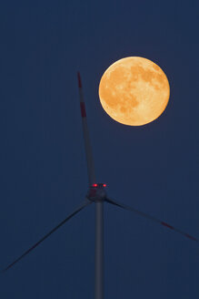 Germany, rise of full moon with wind wheel in the foreground - UMF000794