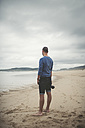 Spain, Ferrol, man with camera standing on the beach - RAEF000335