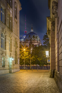 Germany, Berlin, Berliner Dom and TV-Tower seen through a narrow street at night - NKF000355