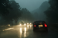 Traffic on county road at rainstorm by twilight - TCF004837
