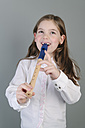 Portrait of little girl playing recorder - ECF001816