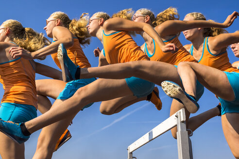 Multiple image of female hurdler jumping over hurdle - STSF000857