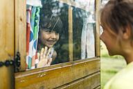 Spain, Asturias, Gijon, Little girls playing through a glass window - MGOF000475