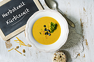 Selfmade pumpkin soup with pumpkin seeds, parsley, a slate and a bun of olives and tomatoes on a wooden table - ODF001221