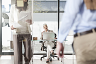 Smiling businesswoman with laptop in office and colleague in background - ZEF007387