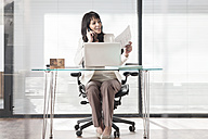 Businesswoman in office on the phone with laptop and documents - ZEF007388
