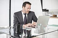 Businessman at desk working at laptop - ZEF007392