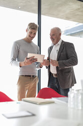 Two colleagues looking at digital tablet in office - ZEF007441