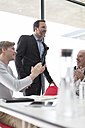 Colleagues applauding for businessman in conference room - ZEF007453