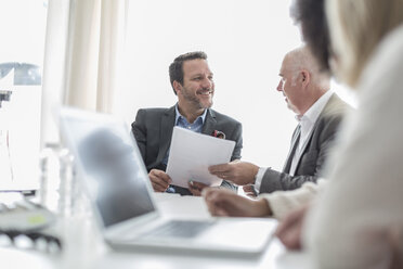 Confident businesspeople with documents and laptop in conference room - ZEF007456