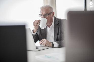 Businessman at desk using laptop - ZEF007120