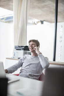 Smiling man in office on cell phone - ZEF007122