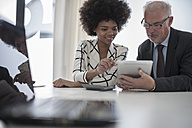 Businessman and woman with digital tablet and calculator - ZEF007095