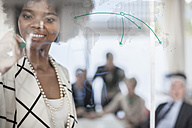 Businesswoman drawing on glass in meeting room - ZEF007104