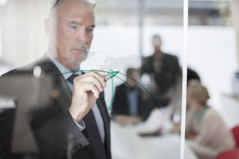 Businessman drawing on glass in meeting room - ZEF007107