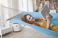 Smiling woman at home lying in hammock using digital tablet - RBF003052