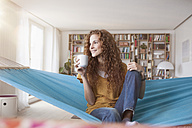 Smiling woman at home sitting in hammock with cup of coffee - RBF003058