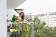Smiling woman watering flowers on balcony - RBF003061