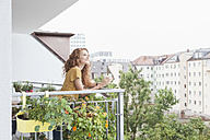 Smiling woman with cup of coffee on balcony - RBF003064