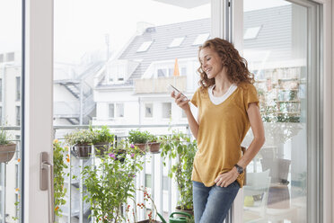 Smiling woman with leaning against balcony door looking on cell phone - RBF003126