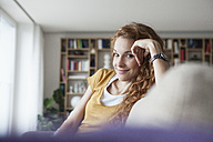 Smiling woman at home sitting on couch - RBF003072