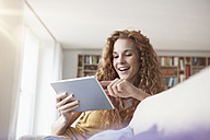 Smiling woman at home sitting on couch using digital tablet - RBF003077