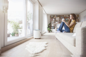 Smiling woman at home sitting on couch looking out of window - RBF003095