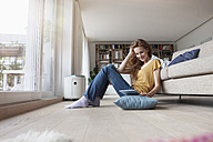 Woman at home sitting on floor holding digital tablet - RBF003102