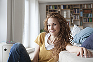 Smiling woman at home sitting on floor - RBF003106