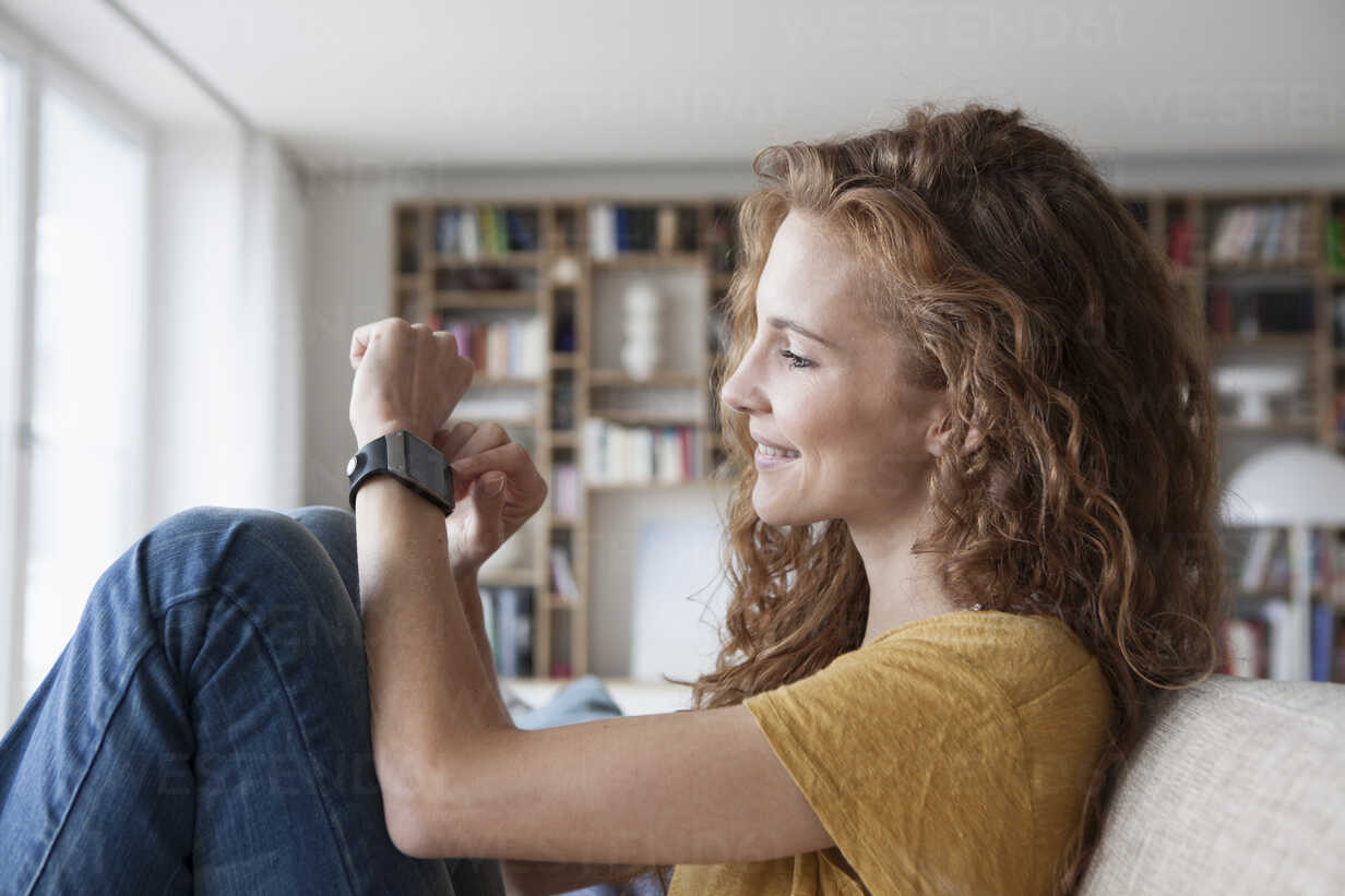 Smiling woman at home sitting on couch looking at smartwatch - RBF003132 - Rainer Berg/Westend61