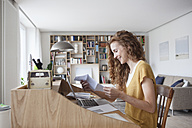Woman at home reading letter on secretary desk - RBF003111