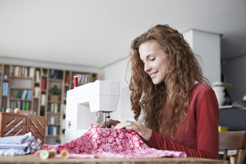 Smiling woman at home using sewing machine - RBF003115