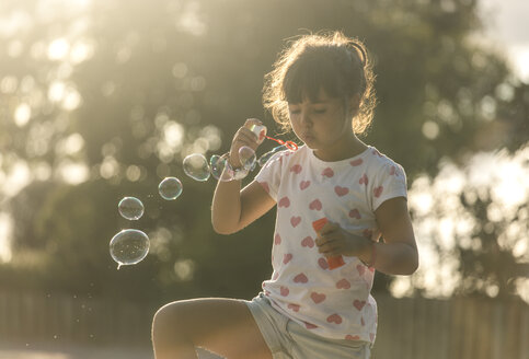 Little girl making soap bubbles in the park at twilight - MGOF000481