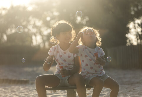 Two little sisters making soap bubbles in the park at twilight - MGOF000483