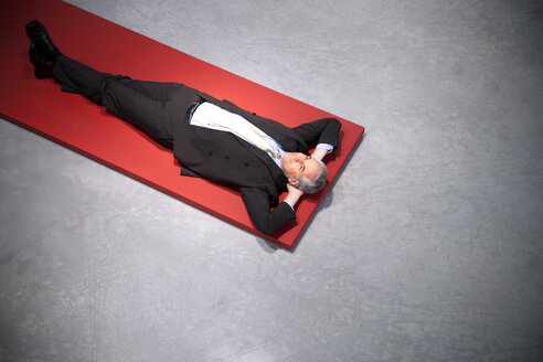 Relaxed businessman lying on floor - TOYF001154