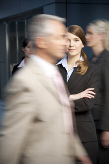 Confident businesswoman with businesspeople passing by - TOYF001236