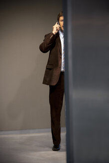 Businessman on the phone behind a wall - TOYF001245